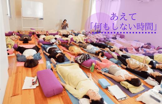 大勢の生徒さんがヨガニードラをしている。前方でサントーシマ香先生が誘導をしている。